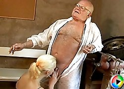 Nubile blonde with cute ponytail giving head to a chubby old grandpa and getting fucked right in his dirty workshop